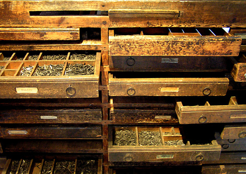 Várias gavetas de madeira subdividididas em várias caixinhas, contento material variado.