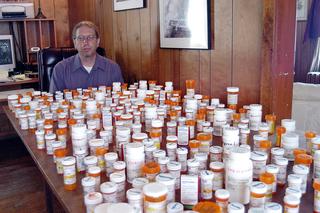 Homem atrás de uma mesa coberta por frascos de analgésicos