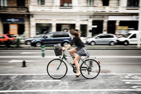 Fotografia de garota andando de bicicleta, vista de perfil.