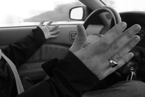 Motorista conversando com o carona e gesticulando.