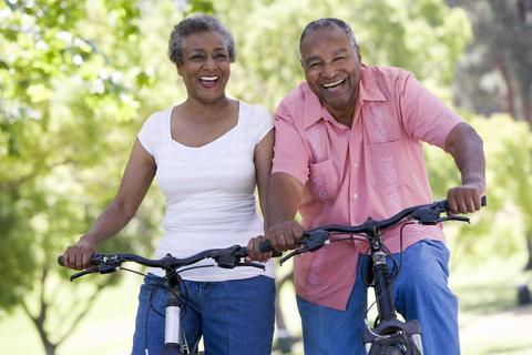 Casal de idosos andando de bicicleta numa área rural.