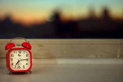 Relógio despertador vermelho numa janela durante o amanhecer.