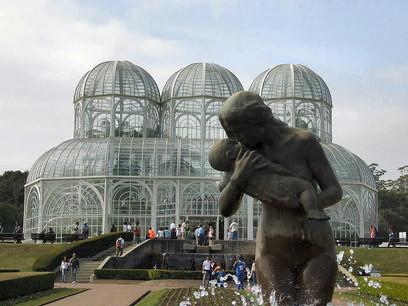 No primeiro plano, a escultura 'A Mãe'. Ao fundo, a estufa do Jardim Botânico Fanchette Rischbieter.