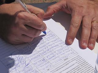 Pessoa assinando um abaixo-assinado.