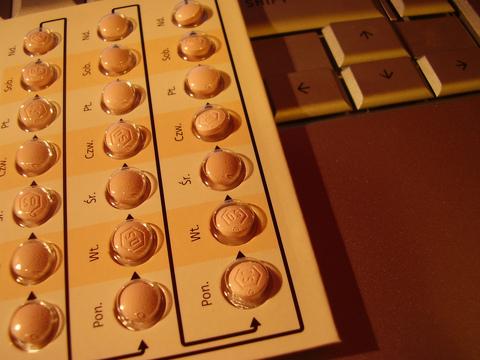 Cartela de pílua anticoncepcional sobre teclado de computador.