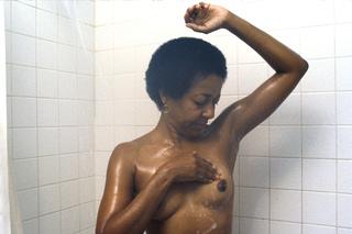 É mostrada uma mulher negra adulta nua da cintura para cima, realizando o auto-exame das mamas. Seu braço esquerdo está elevado e ela está examinando sua mama esquerda com a mão direita.